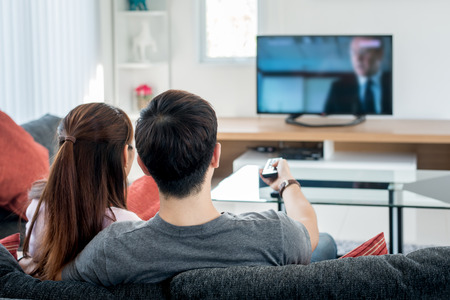 Foto de Rear view of Asian couple watching television in living room - Imagen libre de derechos