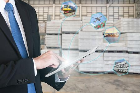 Foto de Logistic concept with businessman hand holding digital tablet shipping icons use for import, export and logistic background. - Imagen libre de derechos
