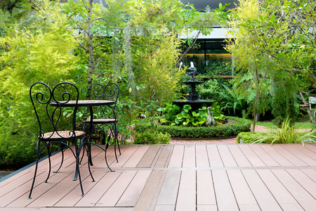 Foto de Black chair in wood patio at green garden with fountain in house. Outdoor garden. - Imagen libre de derechos