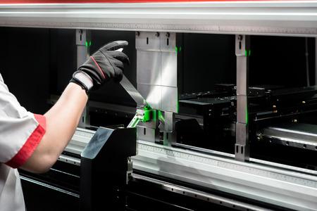 Photo pour Worker at manufacture workshop operating cidan folding machine - image libre de droit