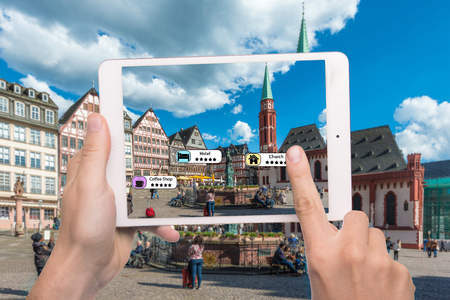 Foto de Hand holding smart phone use AR application to check relevant information about the spaces around customer. Frankfurt City in background. Augmented reality marketing concept. - Imagen libre de derechos