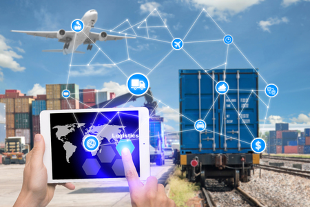 Foto de Hand holding tablet is pressing button Logistics connection technology interface global partner connection for logistic import export background. Business logistics concept , internet of things - Imagen libre de derechos