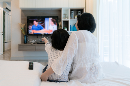 Foto de Happy Asian family mother and daughter sitting on sofa watching flat screen television at living room in home. Family time. - Imagen libre de derechos
