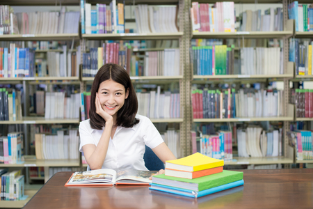 Foto de Asian student in uniform reading book for learning in library at university. One Asian student. - Imagen libre de derechos