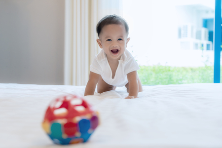 Photo pour Crawling baby boy on bed in bed room at home and he smile to you, Asian baby. - image libre de droit