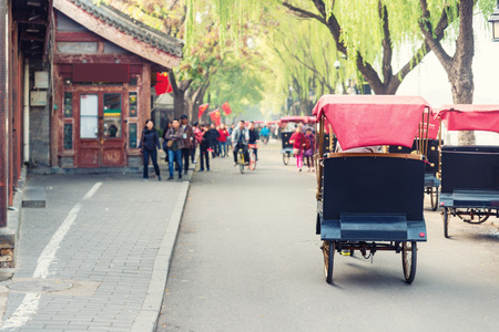 Photo pour Tourists riding Beijing traditional rickshaw in old China Hutongs in Beijing, China. - image libre de droit