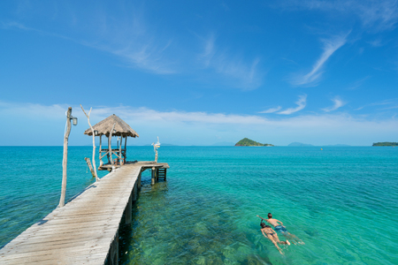 Photo pour Young couple of tourists snorkel in crystal turquoise water near tropical resort in Phuket, Thailand. Summer, Vacation, Travel and Holiday concept. - image libre de droit