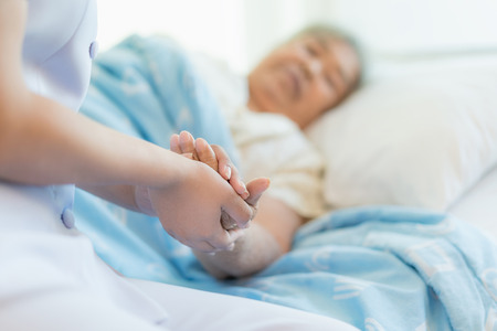Photo pour Nurse sitting on a hospital bed next to an older woman helping hands, care for the elderly concept - image libre de droit