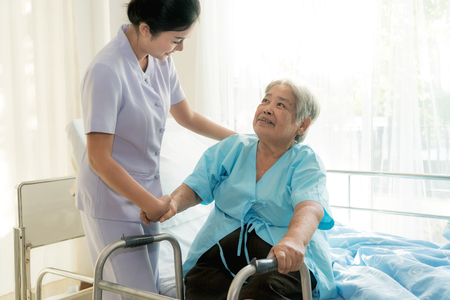 Foto de Asian young nurse supporting elderly patient disabled woman in using walker in hospital. Elderly patient care concept.  - Imagen libre de derechos