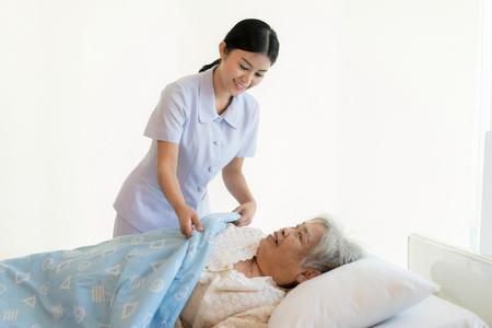 Foto de Asian nurse in elderly care cover her with a blanket for the elderly in nursing home. - Imagen libre de derechos