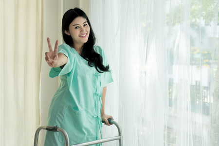 Foto de Young Asian patient woman standing with Folding walker at hospital room showing victory sign for cheerful. - Imagen libre de derechos