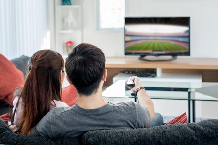Foto de Rear view of Asian couple watching football at television in living room. Football festival concept. - Imagen libre de derechos