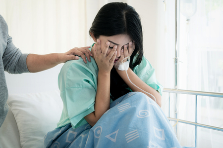 Foto de Asian young woman patient receiving bad news, Woman patient is desperate and crying. Her Mother support and comforting her patient with sympathy. - Imagen libre de derechos