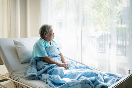 Photo for Asian depressed elderly woman patients lying on bed looking out the window in hospital. Elderly woman patients is glad recovered from the illness. - Royalty Free Image