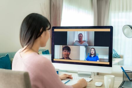 Foto de Back view of Asian business woman talking to her colleagues about plan in video conference. Multiethnic business team using computer for a online meeting in video call. Group of people smart working from home.  - Imagen libre de derechos