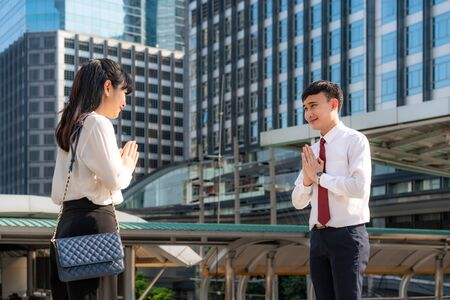 Photo for Pay respect is new novel greeting to avoid the spread of coronavirus. Two Asian young businessman and businesswoman friends meet in font of office building. Instead of greeting with a hug or handshake, they Pay respect instead. - Royalty Free Image