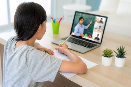 Photo for Asian girl student video conference e-learning with teacher and classmates on computer in living room at home. Homeschooling and distance learning ,online ,education and internet. - Royalty Free Image