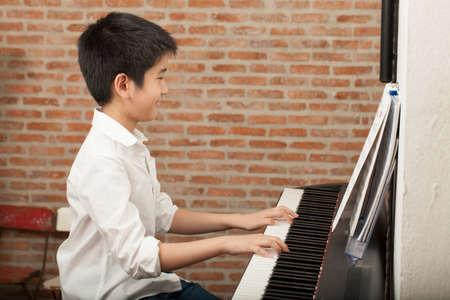 Foto de piano lesson Asian boy kid activity playing piano with notes smiling - Imagen libre de derechos