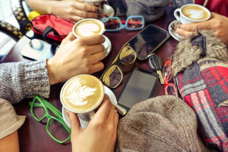 Foto de Hands holding capuccino cup - Group of friends having fun in cafe drinking decorated milk and coffee mug - Concept of friendly business meeting with trendy drinks and mobile phone focus on lowest cup - Imagen libre de derechos