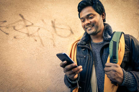 Photo pour Young indian man holding mobile phone - Cheerful asian model next to old urban wall - Soft vintage filtered look focus on person face - image libre de droit