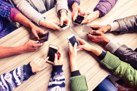 Foto de Top view hands circle using phone in cafe - Multiracial friends mobile addicted interior scene from above - Wifi Connected people in bar table meeting - Concept of teamwork main focus on left phones - Imagen libre de derechos
