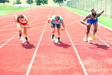 Photo for Runners at start grid front view on red athletics track - Professional sprinters explosive speed training - Concept of preparation for sports events and  international competition - Focus on black guy - Royalty Free Image