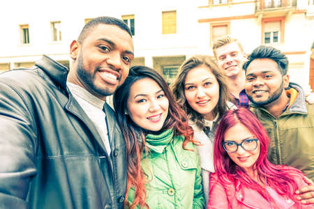 Photo for Multiracial group of friends taking selfie standing on the street at winter season - Happy students smiling at phone camera in a joyful self portrait - Concept of teenage cheerful moments together - Royalty Free Image