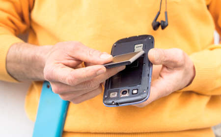 Photo for Man hands inserting mobile phone battery standing outdoors - Male replacing mobile component close up image with main focus on telephone lower part - Royalty Free Image