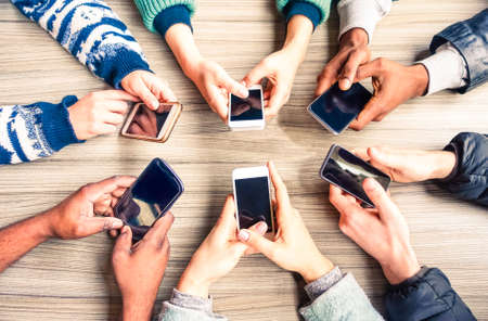 Foto de Hands circle using phones on table top view - Multiracial people holding mobile devices sitting around at office desk - Concept of friends team working and modern communication technology above image - Imagen libre de derechos