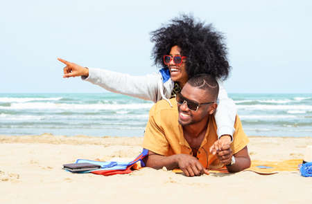 Photo pour Young afro american couple  pointing finger relaxing on beach - Cheerful african friends having fun at day on blue ocean background - Concept of lovers happy moments on summer holiday - Vintage filter - image libre de droit