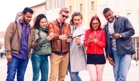 Photo pour Multicultural group of friends looking  phone with surprised face - Multiracial teenagers having fun using smartphone standing in the street at winter - Concept of addiction to modern technology - image libre de droit