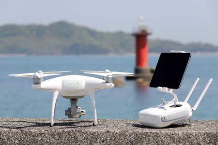 Foto de drone and remote controller with monitor on concrete jetty - Imagen libre de derechos