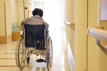 Foto de Back view of senior or elderly woman on wheelchair at hospital hallway - Imagen libre de derechos