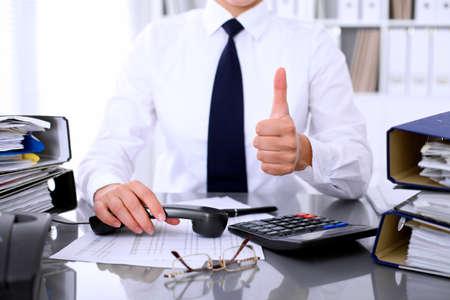 Foto de Close up of business woman showing ok sign while making report, calculating or checking balance. - Imagen libre de derechos