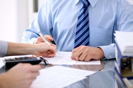 Foto de Bookkeepers or financial inspector making report, calculating or checking balance. Audit concept - Imagen libre de derechos
