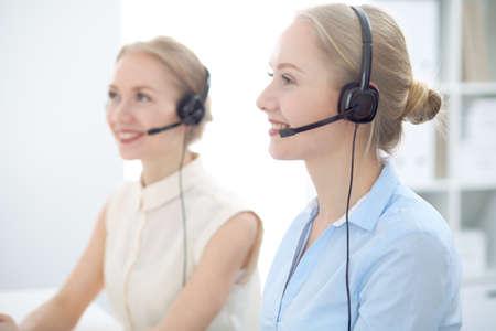 Foto de Image of bright call center. Focus on young beautiful woman in a headset - Imagen libre de derechos