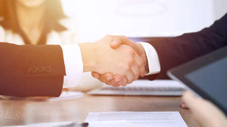 Photo pour Close up of business people shaking hands at meeting or negotiation in the office. Partners are satisfied because signing contract - image libre de droit