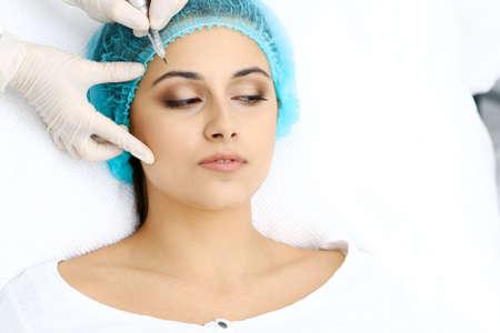 Foto de Professional beautician doing eyebrow tattoo at woman face. Permanent brow makeup in beauty salon, closeup.  Cosmetology treatment - Imagen libre de derechos