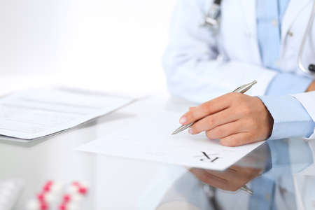 Photo pour Doctor woman filling up prescription form while sitting at the desk in hospital close-up.  Physician at work and ready to give an advice to help patient. Healthcare, insurance and excellent service in medicine concept - image libre de droit