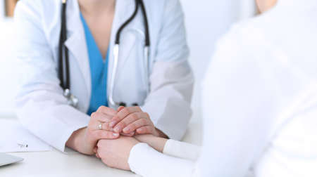 Photo pour Medicine doctor hand reassuring her female patient closeup. Medicine, comforting  and trusting concept in health care - image libre de droit