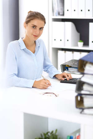 Photo pour Woman bookkeeper or financial inspector calculating or checking balance, making report. Internal Revenue Service at work with financial document. Tax and audit concept - image libre de droit