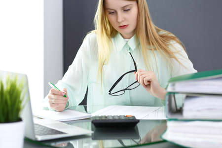 Photo pour Bookkeeper or financial inspector woman making report, calculating or checking balance. Audit and tax service concept. Green colored image background - image libre de droit