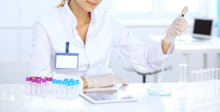 Foto de Female scientific researcher or blood test assistant at work in laboratory. Science, medicine and pharmacy concept - Imagen libre de derechos