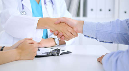 Photo for Doctor and patient shaking hands. Family couple at medical exam, just hands at the table. Medicine concept - Royalty Free Image