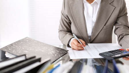 Photo pour Unknown bookkeeper woman or financial inspector  making report, calculating or checking balance, close-up. Business portrait. Audit or tax concepts - image libre de droit