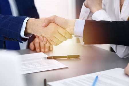 Photo for Business people shaking hands, finishing up a papers signing. Meeting, agreement and lawyer consulting concept - Royalty Free Image
