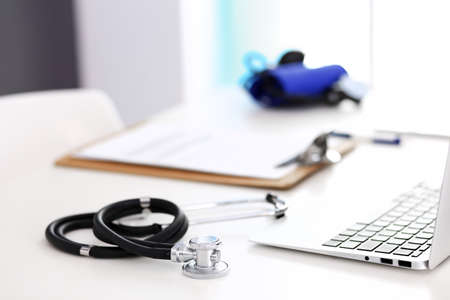 Photo pour Closeup of stethoscope. Female doctor fills up medical form while sitting at the desk in hospital. Healthcare, workplace and cardiology in medicine concept - image libre de droit
