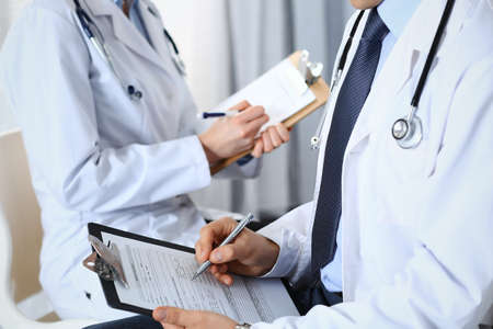 Photo pour Two unknown doctors filling up medical form on clipboard, just hands closeup. Physicians asking question to patient or discussing medication program. Healthcare, insurance and medicine concept - image libre de droit