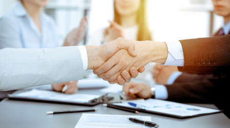 Photo pour Business people shaking hands at meeting while theirs colleagues clapping and applausing. Group of unknown businessmen and women in modern white office. Success teamwork, partnership and handshake concept. - image libre de droit
