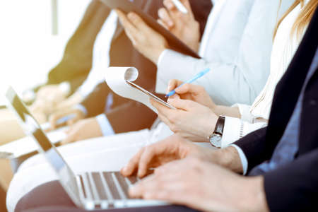 Photo pour Business people working at meeting or conference, close-up of hands. Group of unknown businessmen and women in modern white office. Teamwork or coaching concept - image libre de droit